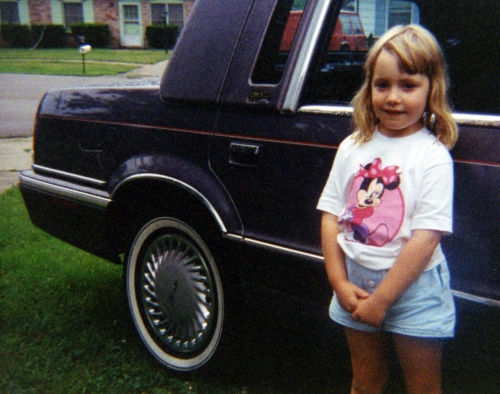 Young girl standing next to car